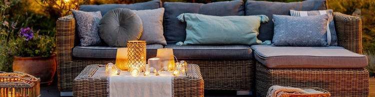Gartenlounge bei Abendstimmung mit gemütlichen Kissen und Teelichtern