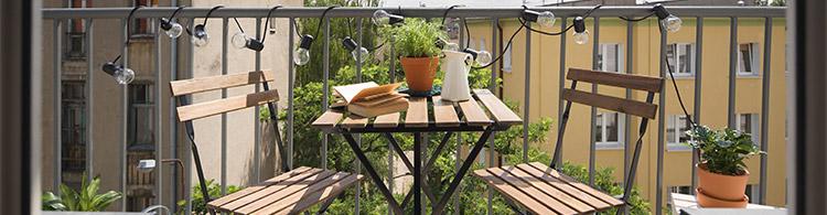 Holzmöbel auf dekoriertem Balkon als Symbol für Balkonmöbel