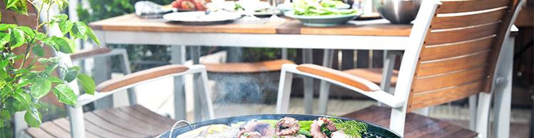 Grill steht vor Gartenmöbeln als Symbol für Gartenmöbel, die bei Grillparty nicht fehlen dürfen
